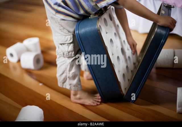 Six year old boy packs toilet rolls into suitcase Mixed race indian ethnic and caucasian - Stock-Bilder