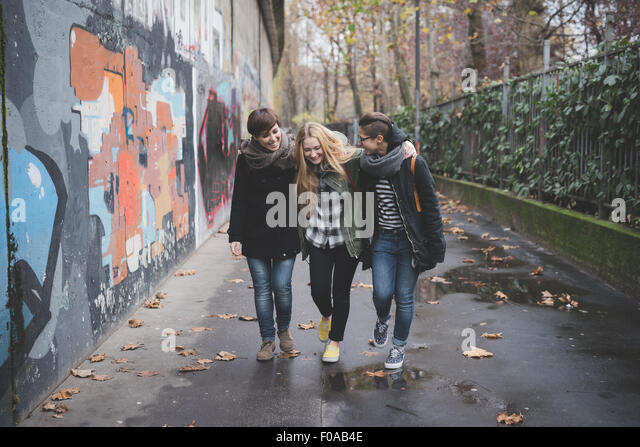 Three sisters walking by graffiti wall - Stock Image