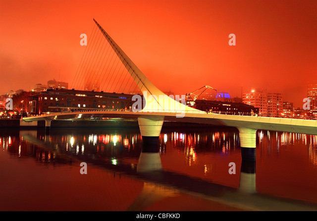 Bridge of the Woman view at stormy orange sunset, with city silhouette at background. - Stock-Bilder