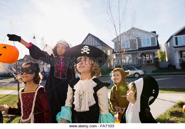 Kids in Halloween costumes trick or treating neighborhood - Stock Image
