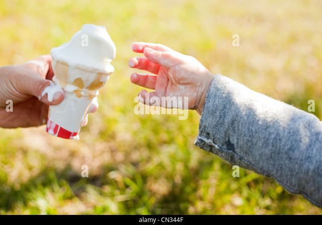 Toddler taking ice cream cone - Stock-Bilder