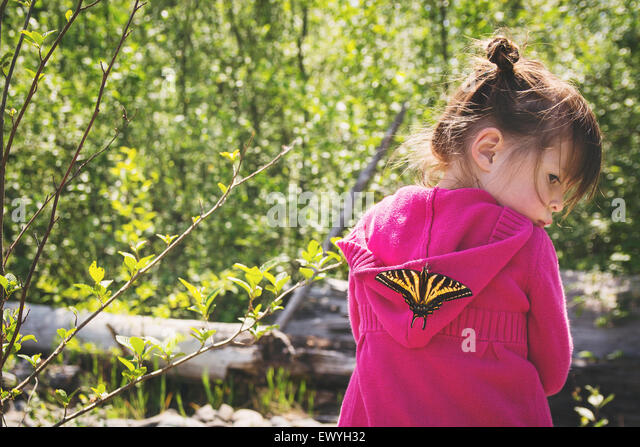Young girl with a butterfly on her back - Stock Image
