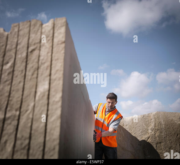 Quarry worker inspecting cut stone, low angle view - Stock-Bilder