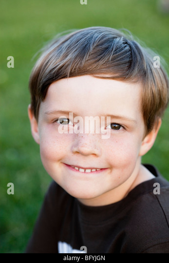 Shy Boy Smiling To Camera - Stock Image
