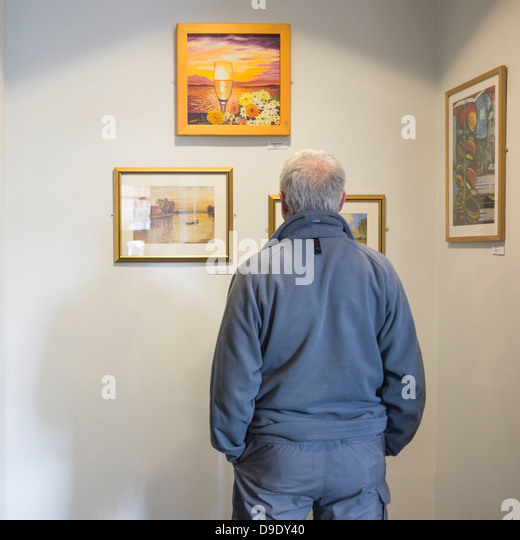 Rear view of a man looking at the art on show at the opening of an exhibition of amateur paintings, Wales UK - Stock-Bilder