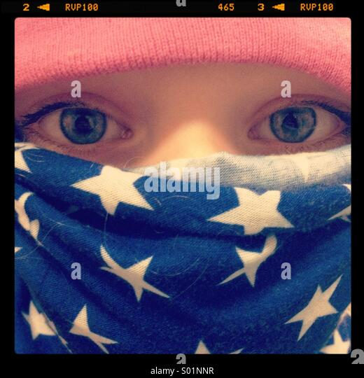 A close up of a little girl protected against the cold with a flag scarf and pink hat - Stock Image