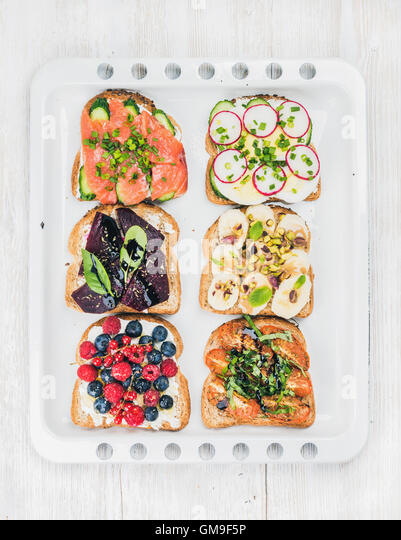Sweet and savory breakfast toasts assortment. Sandwiches with fruit, vegetables, eggs, smoked salmon on white baking - Stock Image