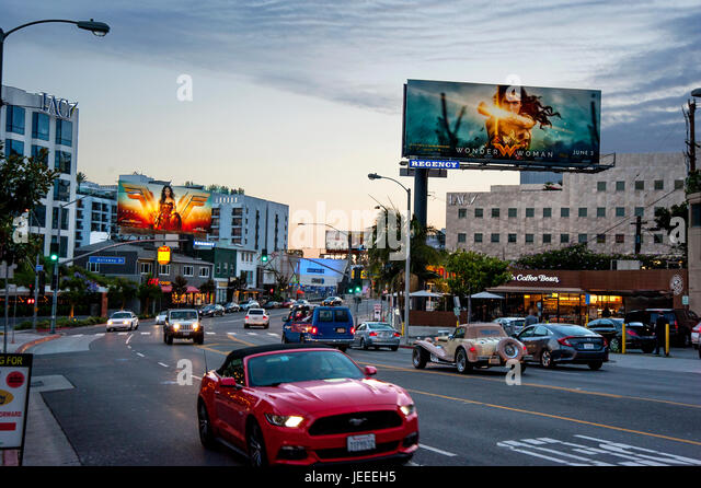 The Sunset Strip at dusk with lit billboards promoting the movie Wonder Woman in Los Angeles, CA. - Stock Image