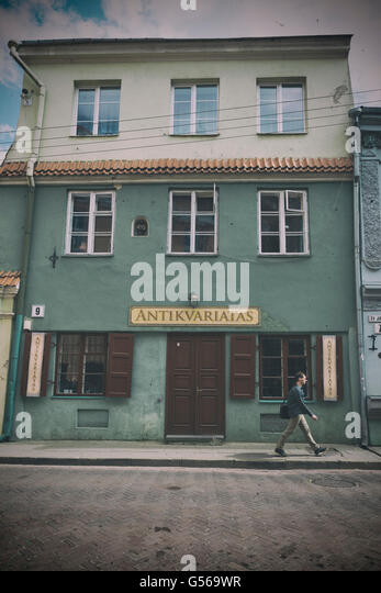 VILNIUS, LITHUANIA - JUNE 8, 2016: An unidentified man walks in front of an antiquarian shop. vintage processing - Stock-Bilder