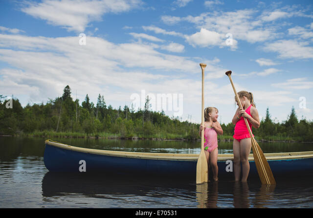 Two young sisters chatting next to canoe on Indian river, Ontario, Canada - Stock Image
