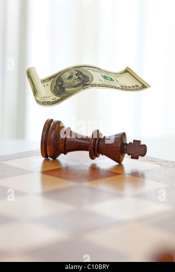 chess game king knocked over covered with a floating one hundred dollar bill. - Stock Image