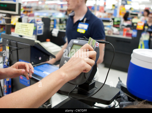 Female consumer uses, swipes credit card to make purchases at Wal-Mart Supercenter store in San Marcos, Texas - Stock Image
