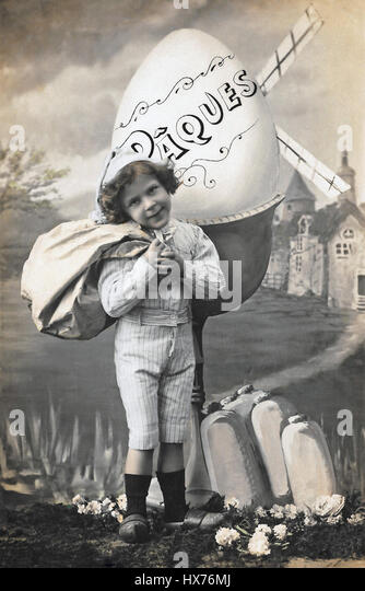 Archival postcard photograph of a young boy and a giant Easter egg, circa 1910. - Stock Image