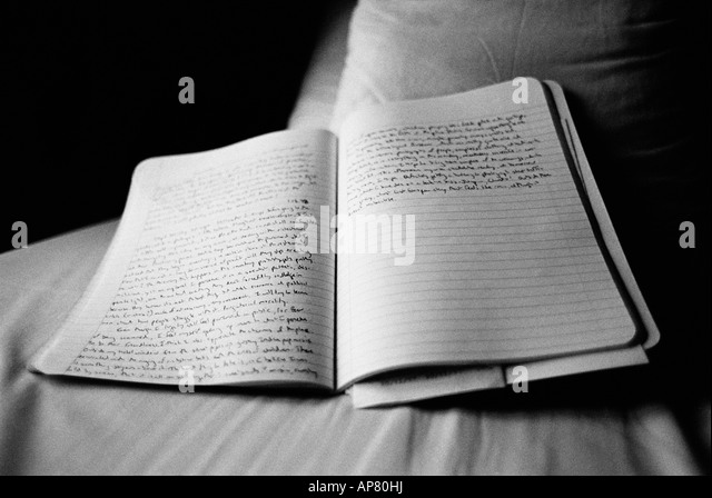 open journal on bed - Stock Image