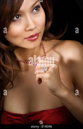 A beautiful woman wearing a diamond ring and rhinestone studded necklace. - Stock Image