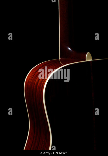 Acoustic guitar against black background - Stock Image