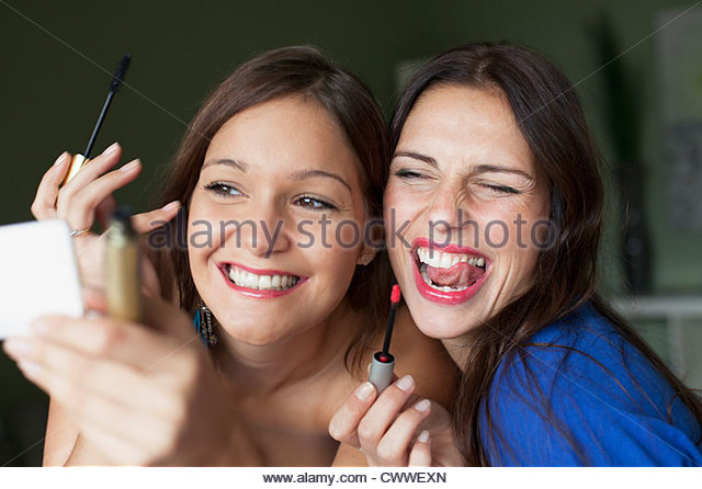 Smiling women applying makeup in mirror - Stock Image