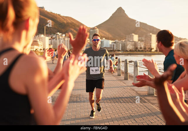 Young male athlete being applauded by supporters as he reaches the finishing line of a running race. Young people - Stock Image
