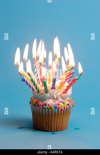Birthday cupcake with lots of burning candles - Stock Image
