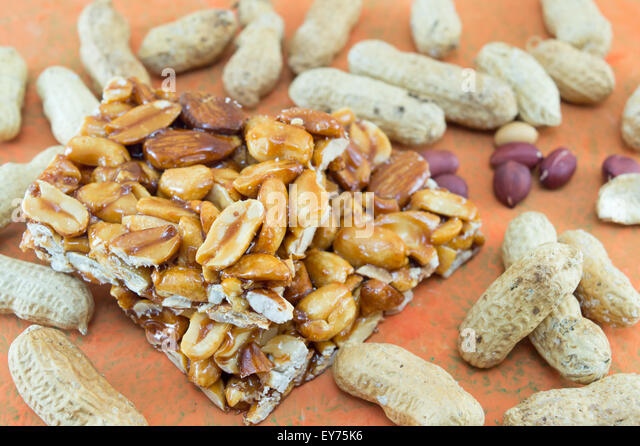 Honey bar with peanuts almonds and hazelnuts surrounded by bunch of roasted and raw peanuts on orange background - Stock Image