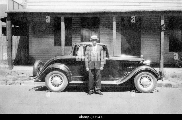 Full length portrait of African American man standing in front of a car outdoors, wearing a suit and hat, neutral - Stock Image