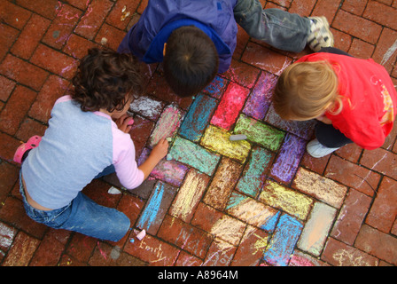 Little kids play with sidewalk chalk on Carroll Avenue Takoma Park MD - Stock Image