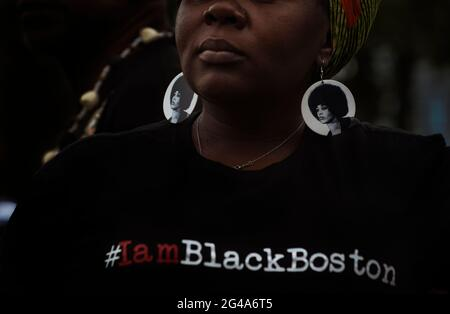 Juneteenth 2021, Dorchester Center, Boston, Massachusetts USA.  19/06/2021.  About 100 people gathered to celebrate Juneteenth, Juneteenth has been celebrated in the black community since the 1800's and 2021 is the first time Juneteenth became an American national holiday. Photo shows Latoya, 42, a female African-American resident of the Dorchester area of Boston, Massachusetts USA during the celebration.  Latoya is wearing earrings with a portrait of Angela Davis, a famous Black female activist and university professor. Credit: Chuck Nacke/ Alamy Live News - Stock Image