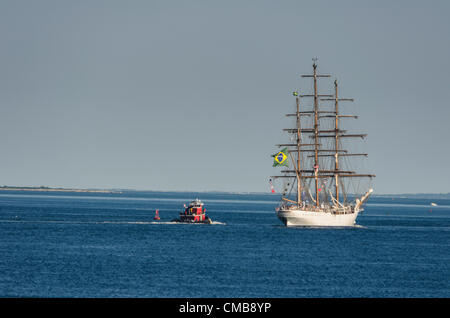 New London, Connecticut, USA - July 9, 2012: The Brazilian tall ship Cisne Branco with signal flags and the flag of Brazil flying, sails away from Fort Trumbull toward home with a red tugboat behind it as OpSail 2012, commemorating the bicentennial of the War of 1812 and the penning of the US national anthem, the Star Spangled Banner draws to a close. - Stock Image