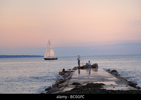 Father and child fishing from a pier dock Connecticut coast at twilight with sailboat passing by Niantic East Lyme Connecticut - Stock Image
