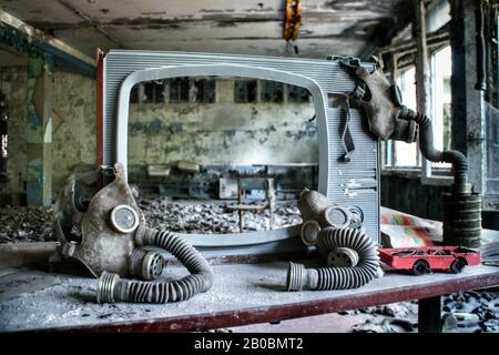 Soviet-era gas masks are hung up on a weathered TV screen in an abandoned building in Pripyat, Ukraine, site of the 1986 Chernobyl nuclear desaster. - Stock Image