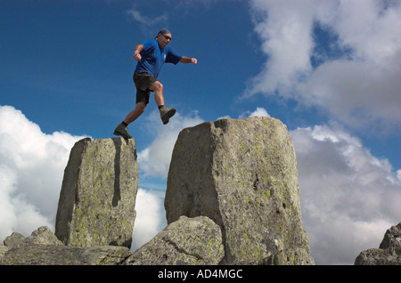 A climber jumping on Adam and Eve on the summit of Tryfan in Snowdonia North Wales - Stock Image