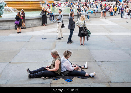 London UK, 15 Aug, 2018, While it ranged from cloudy to partly sunny, some managed to find a quiet place in busy Trafalgar Square.  Perhaps the flat surface reminded them of their home in Kansas. Credit: Jeff Greenberg/Alamy Live News - Stock Image