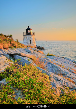 Castle Hill lighthouse light house at twilight golden sunset with rocky cliffs over Narragansett Bay Newport Rhode Island US HDR - Stock Image