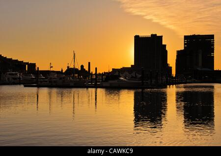 A dramatic and beautiful sunrise with buildings and boats in silhouette reflected in the waters of Baltimore's Inner Harbor Harbour Maryland, USA. Friday 27th April 2012. - Stock Image