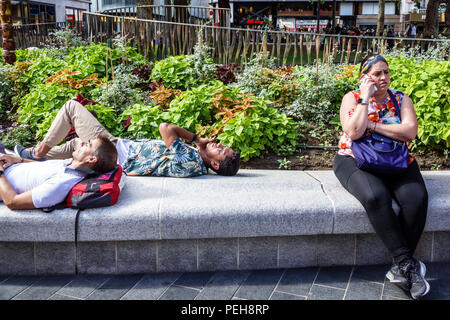 London UK, 15 Aug, 2018, While it ranged from cloudy to partly sunny, some managed to find a quiet place in busy Leicester Square. Credit: Jeff Greenberg/Alamy Live News - Stock Image
