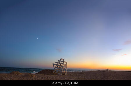 Summer in the Hamptons. Ponquogue Beach, Hampton Bays, New York blue hour sunset lifeguard chairs, sliver of the moon, Venus. - Stock Image