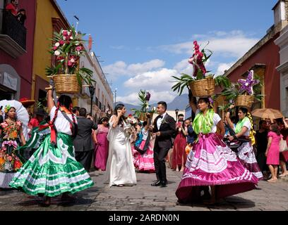 Bride and groom framed by woman in traditional outfit part of Traditional wedding parade (Calenda de Bodas) on the streets of Oaxaca. - Stock Image
