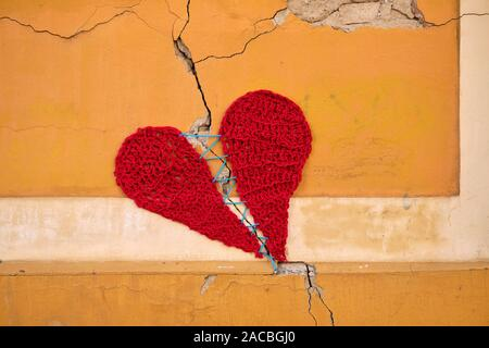 Concrete wall with a crack, covered by a wool knitting of two parts of heart held together by a single string. - Stock Image