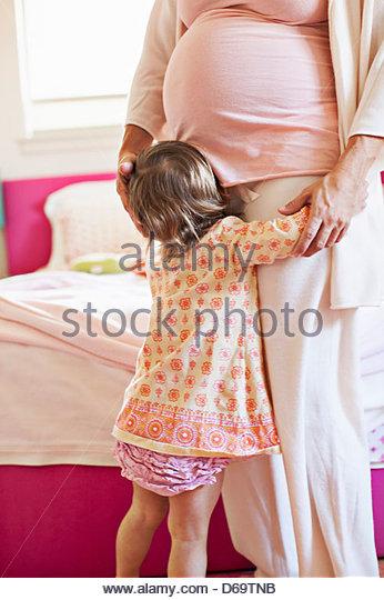 Toddler girl hugging pregnant mother - Stock-Bilder