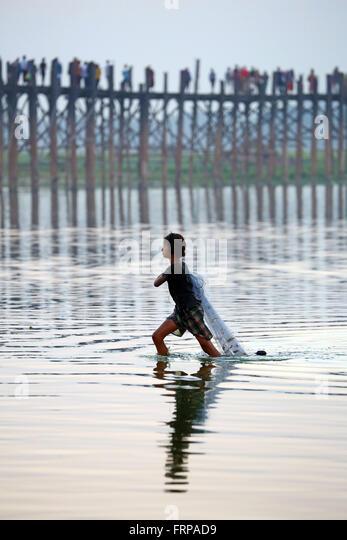 The U Bein  Bridge with a fisherman walking across the Taungthaman Lake in Amarapura, Mandalay, Myanmar (Burma) - Stock-Bilder