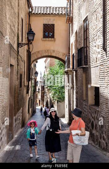 Spain Europe Spanish Hispanic Toledo narrow steep street alley Asian mother daughter grandmother family exploring - Stock Image