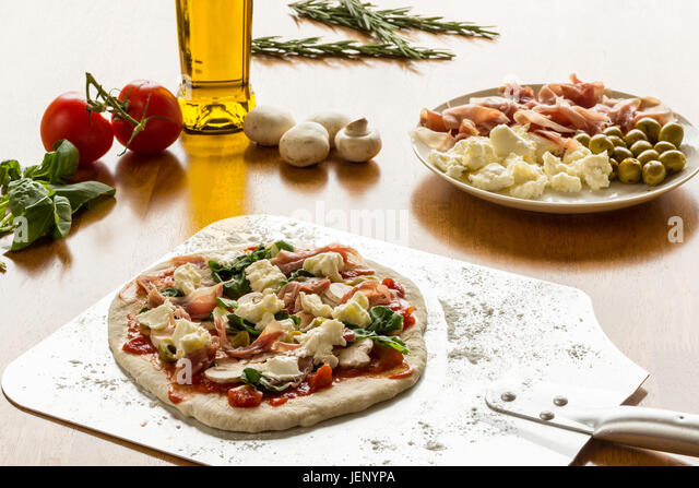 A Topped Pizza on a peel ready for the oven - Stock Image