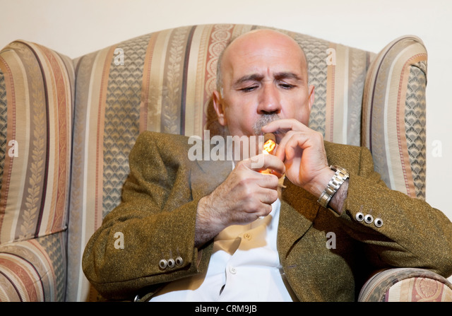Mature man igniting cigar while sitting on armchair - Stock Image