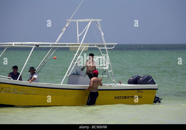 Fishing boat and men in shallow water, Caribbean Sea, Holbox island, Quintana Roo, Yucatán Peninsula, Mexico, - Stock Image
