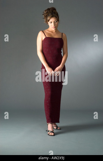 sad shy elegantly dress woman in studio full body portrait - Stock Image