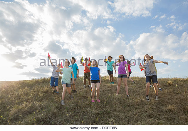Schoolchildren aiming paper airplanes on hillside - Stock Image
