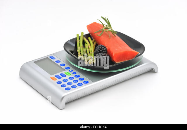 Healthy nutritious raw food on a scale, isolated on white. - Stock Image