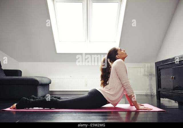 Side view of a fit young woman doing yoga exercise on mat at home. Female stretching her back while lying on floor. - Stock Image