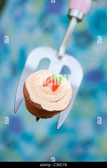 Carrot cupcake on gardening fork selective focus - Stock Image