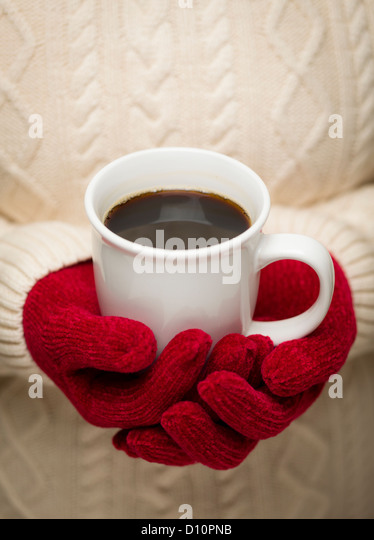 Woman in Sweater with Seasonal Red Mittens Holding a Warm Cup of Coffee. - Stock Image